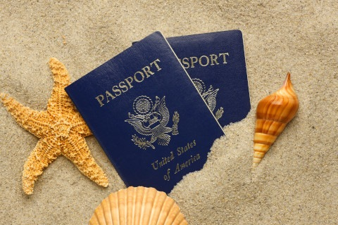 US Passport on a sandy beach with seashells