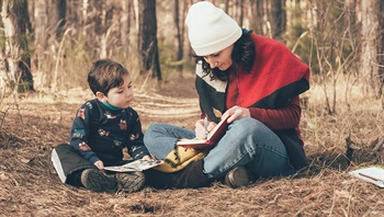 An adult and child sketch in a book outside.