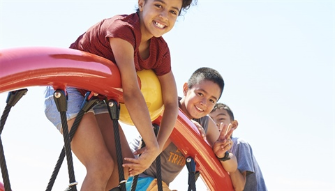 Three youth smiling at a playground.