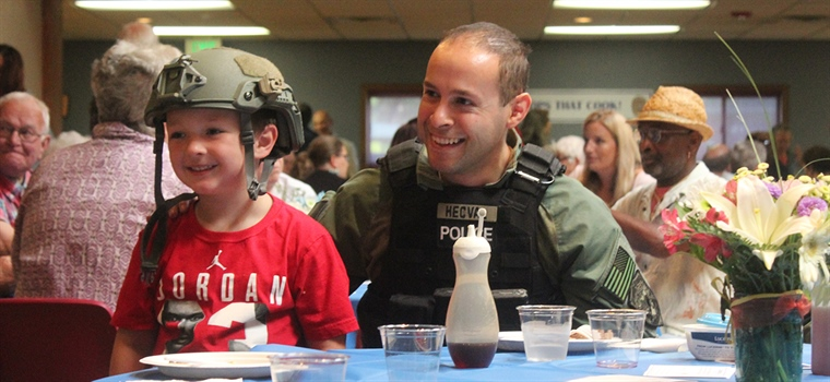 A police officer sits with a child during the fundraiser.
