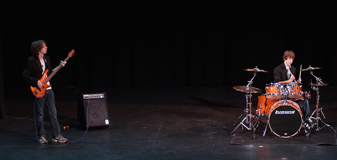 Two performers play guitar and drums.