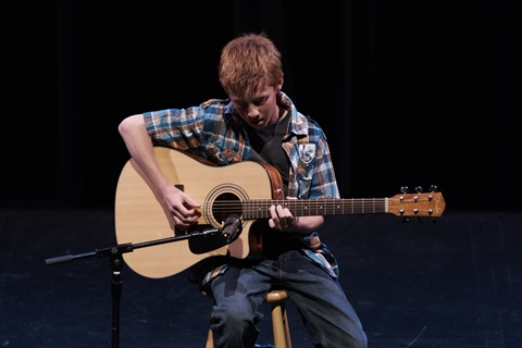 A performer plays guitar.