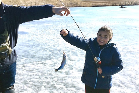 Youth holds up a fish on frozen lake.