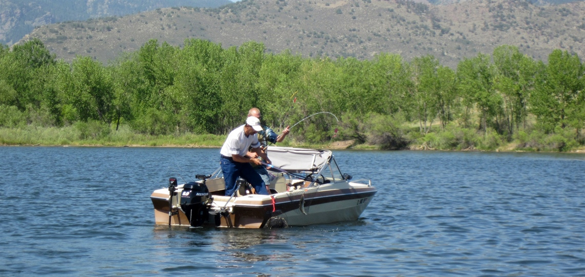 Two people catch a trout in a boat during the tournament.