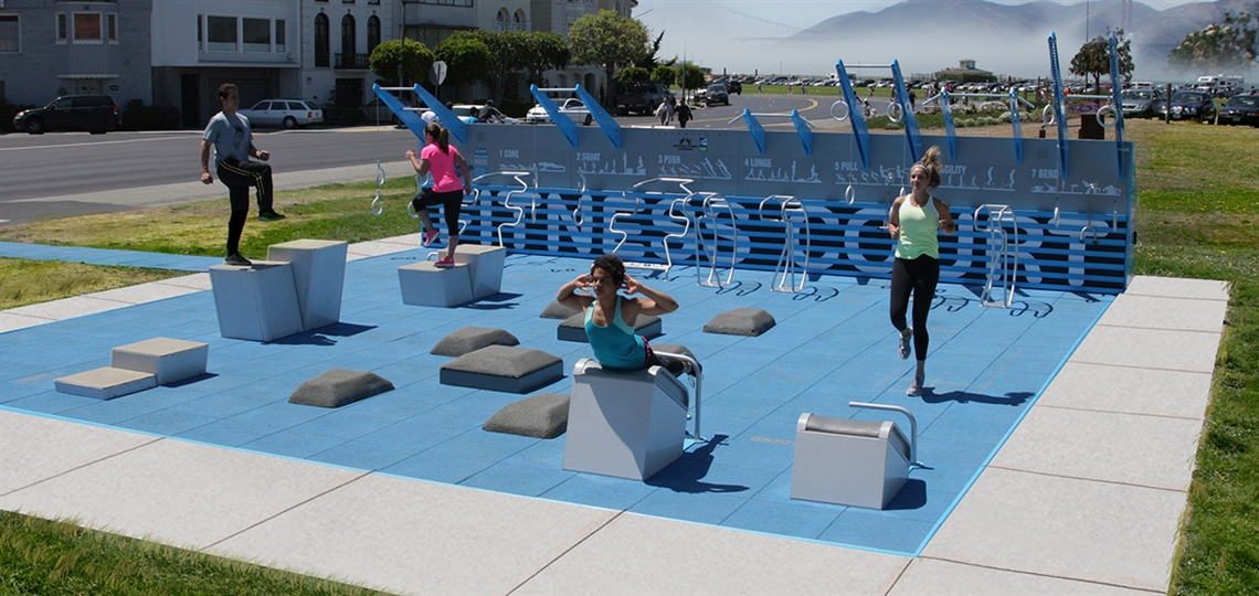 Three people use an outdoor fitness court.