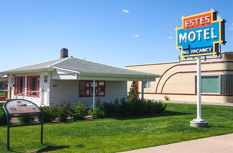 A front view of the Estes Motel building and sign.