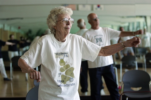 A SilverSneakers class takes place in a fitness room.