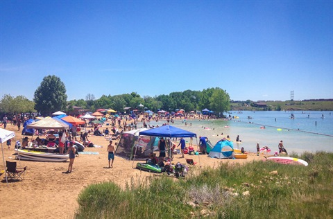 A crowd spends time on the Bear Creek Lake Park beach.
