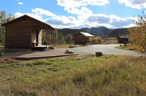 Three cabins are pictured within the Bear Creek Lake Park campground.