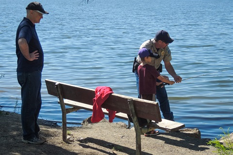 A park ranger assists a child in fishing at Bear Creek Lake Park.