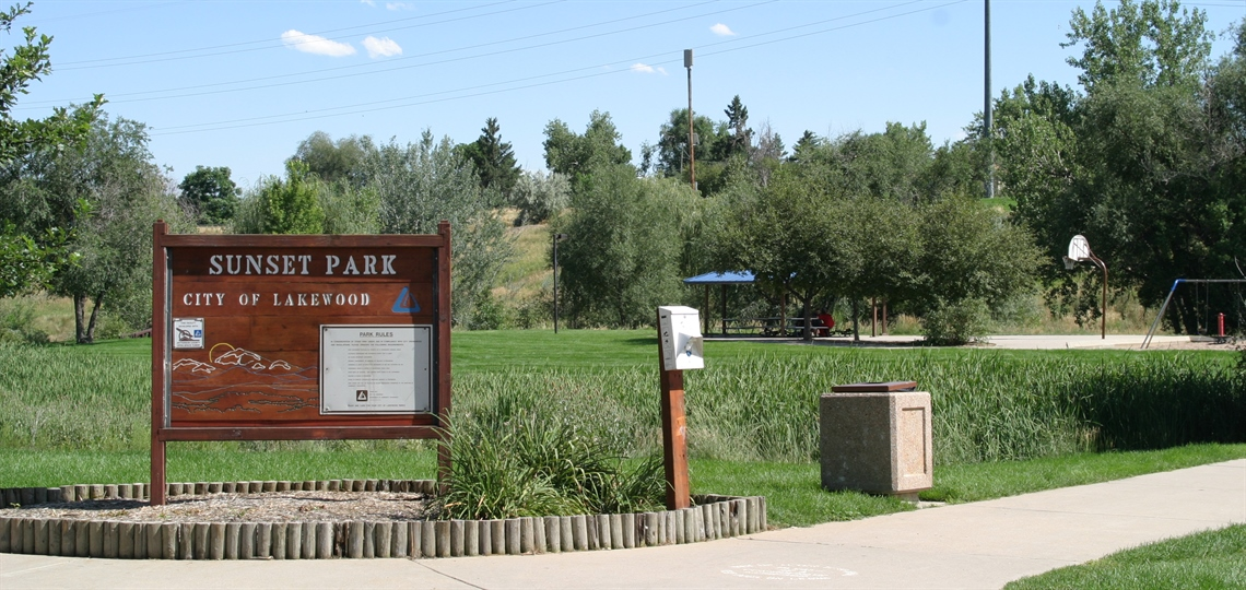 Sunset Park sign with picnic shelter and basketball court in background