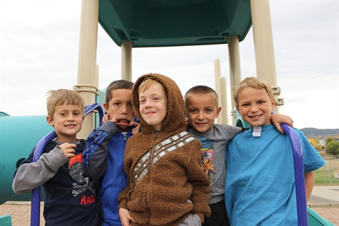A group of children pose at a city park.