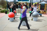Class participants use exercise balls during an outdoor class.