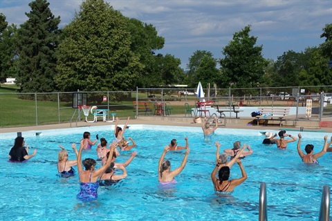 An outdoor aqua fitness class takes place in a city pool.