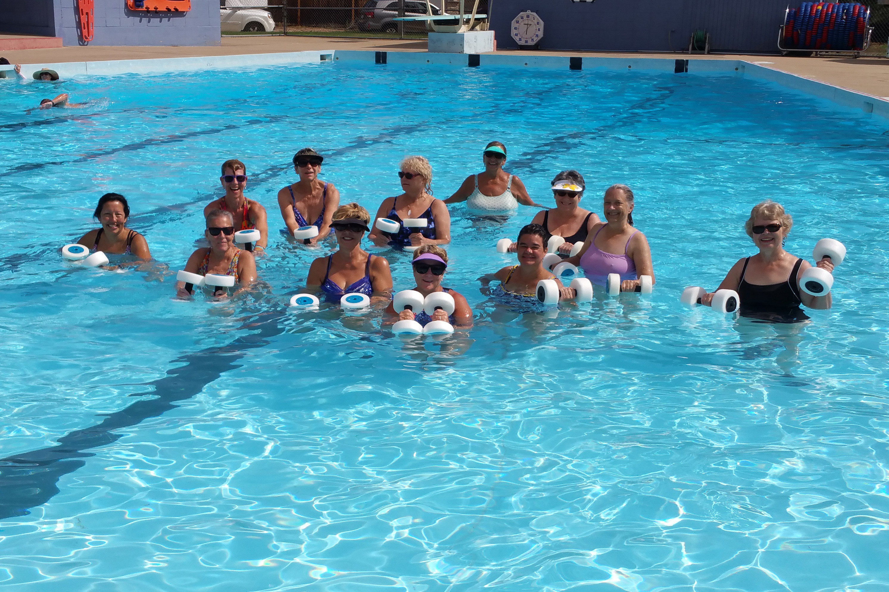 An aqua fitness class with weights takes place in a city pool.