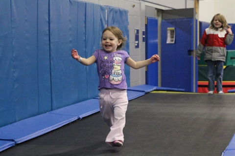 A child runs through the link gymnastics facility during a party.