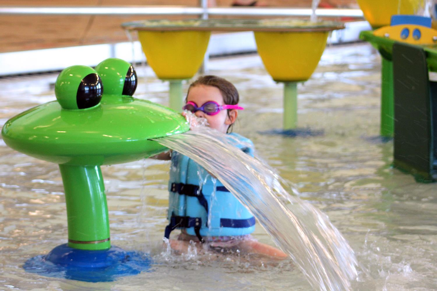 A child plays with a splash feature at the Link pool.