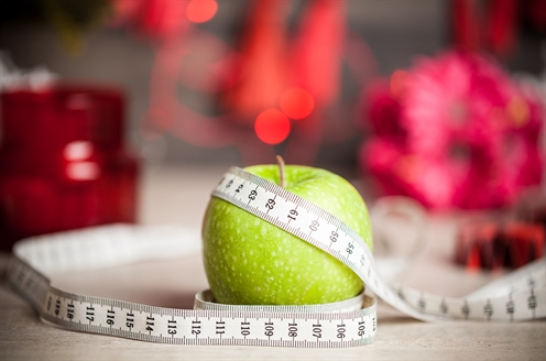 An apple sits on a table with a measuring tape.