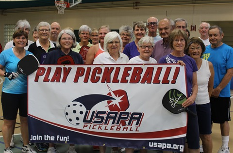 Pickleball participants hold a