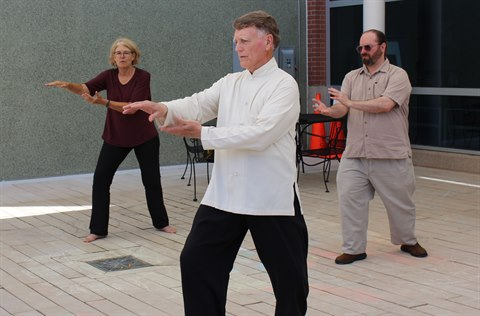 Tai Chi class participants perform movements outside.