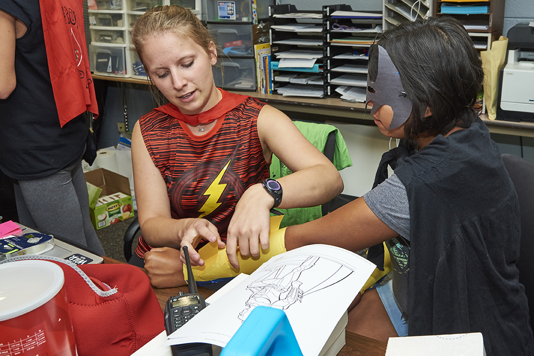 A staff member and Camp Paha participant create a superhero costume.