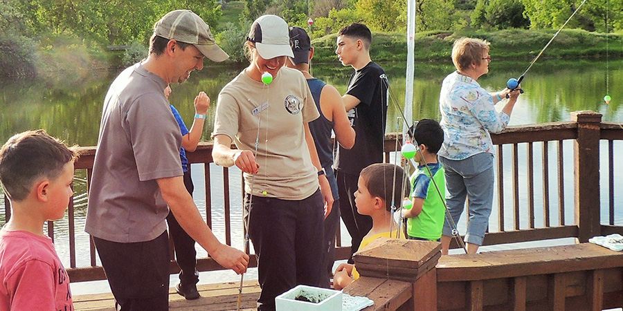 Nature Ambassadors assist children fishing.