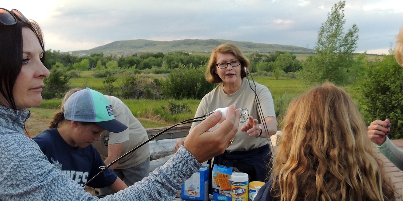 A nature guide helps families make smores at a campfire program.