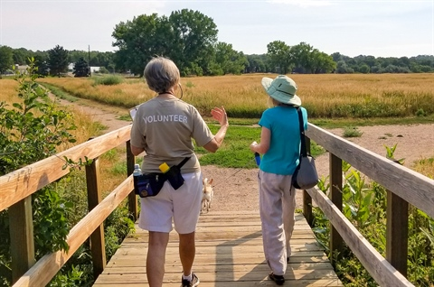 A parks volunteer guides a visitor through the area.
