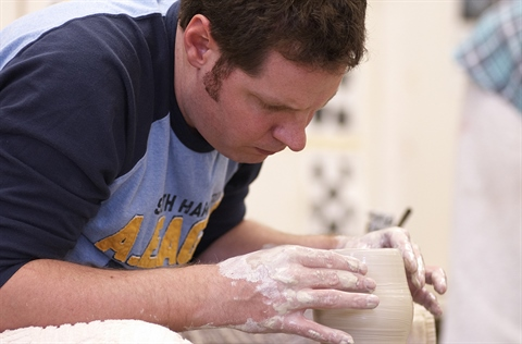 A resident creates pottery during an adult class.