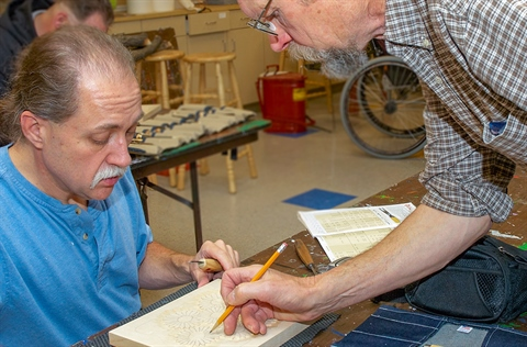 A wood carving instructor assists a student.