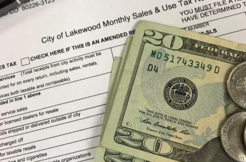 A Lakewood Sales and Use Tax return with money and a pen laying on top.