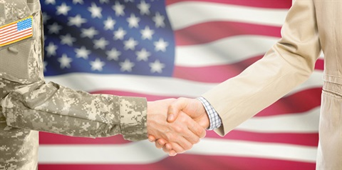 Handshake in front of a Flag