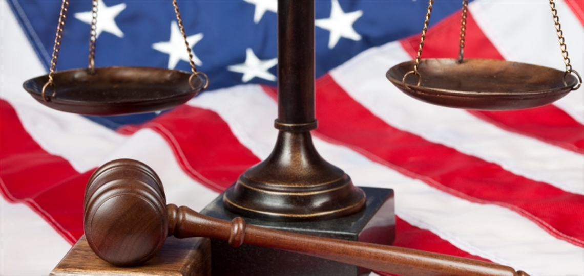 Justice scales with gavel in front with a flag background.