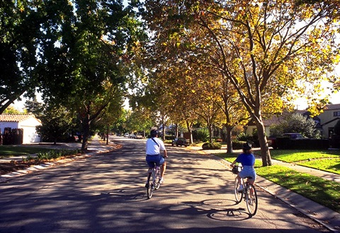 Two people are enjoying a bike ride in a neighborhood.